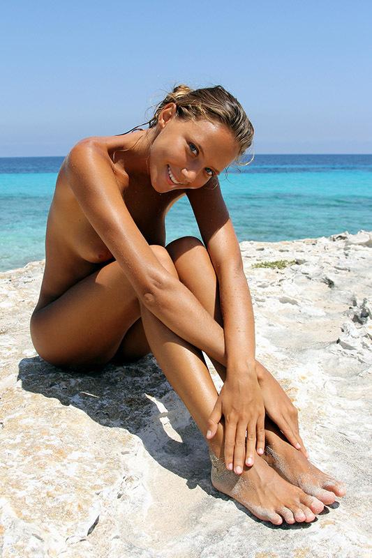 Загорелая туристка купается на нудистском пляже 11 фото
