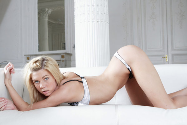 Худенькая блондинка стягивает нижнее белье с себя на диване 1 фото