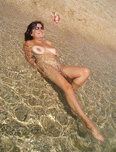 Голая женщина на берегу моря в жаркую погоду