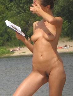 Нудистка читает литературу прямо на пляже летом