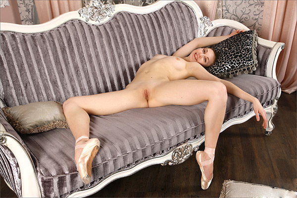 Голая гимнастка стягивает штанишки и позирует на диване 9 фото