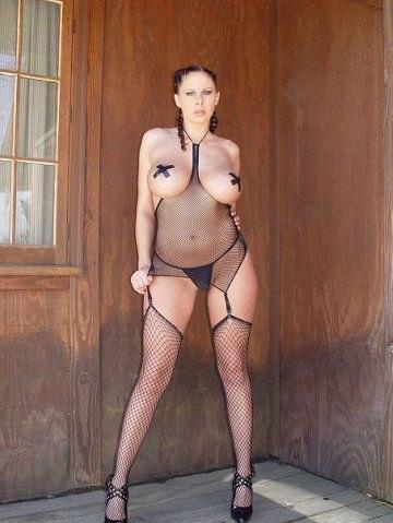 Милфа с большими дойками оголилась у себя в саду 14 фото