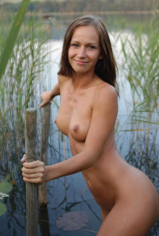 Милашка сексуально двигается у водоема, сверкая титьками 7 фото