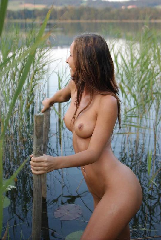 Милашка сексуально двигается у водоема, сверкая титьками 4 фото