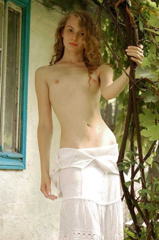 Обнаженная кокетка в чулках позирует в саду 1 фото