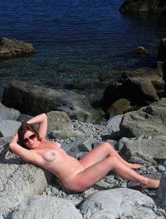 Раздетая дама отдыхает на свежем воздухе у моря на валунах