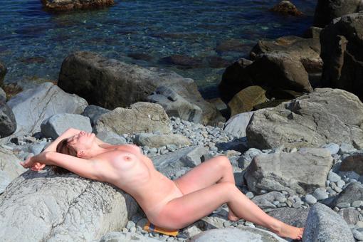 Раздетая дама отдыхает на свежем воздухе у моря на валунах 4 фото