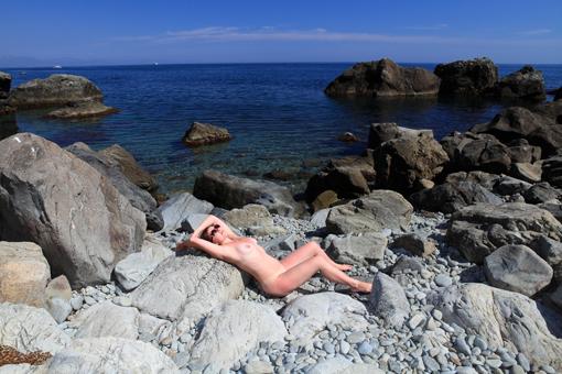 Раздетая дама отдыхает на свежем воздухе у моря на валунах 2 фото