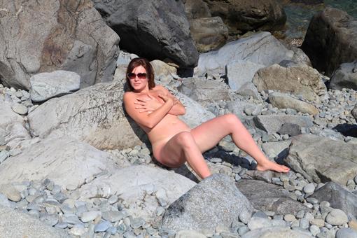 Раздетая дама отдыхает на свежем воздухе у моря на валунах 5 фото