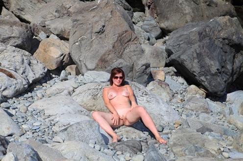 Раздетая дама отдыхает на свежем воздухе у моря на валунах 6 фото
