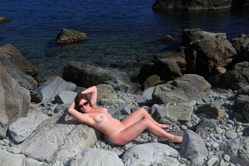 Раздетая дама отдыхает на свежем воздухе у моря на валунах 3 фото