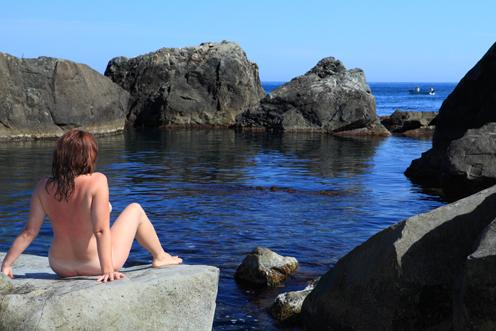 Раздетая дама отдыхает на свежем воздухе у моря на валунах 7 фото