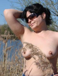 Зрелая дама оголила небольшие сиськи на природе