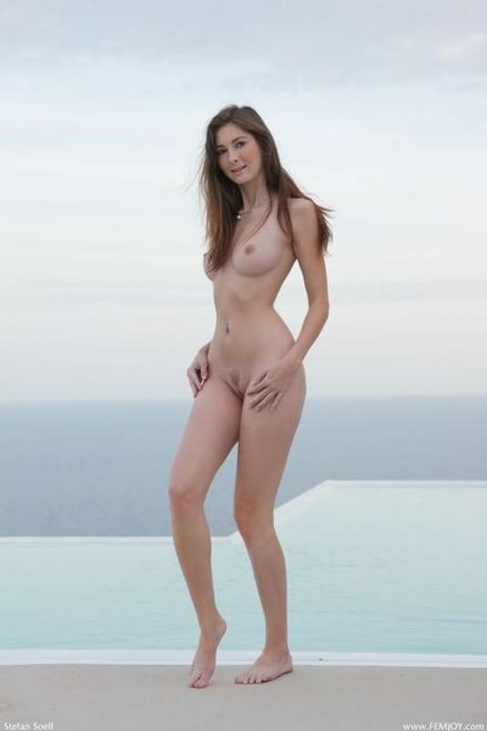 Модель с пирсингом в пупке голышом позирует на лоджии 12 фото