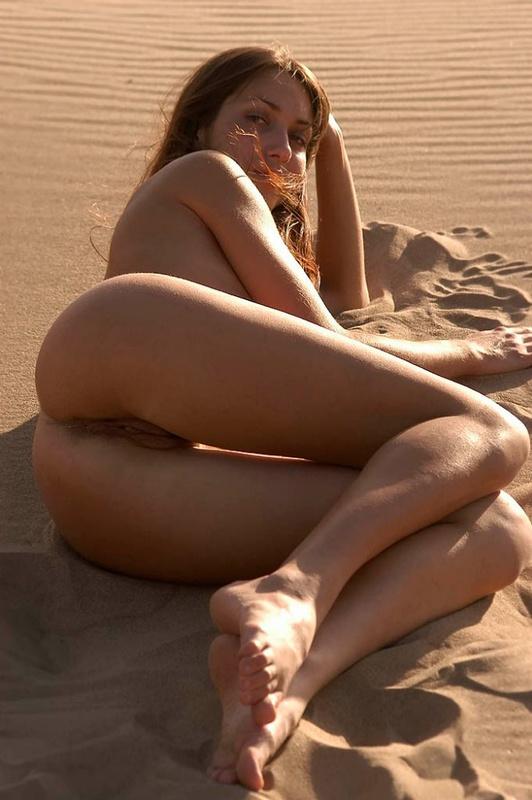 Голая молодуха позирует на песке 11 фото