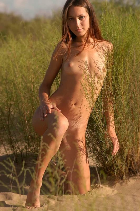 Голая молодуха позирует на песке 4 фото