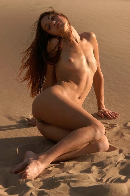 Голая молодуха позирует на песке 12 фото