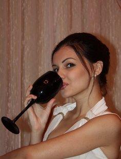 Красивая брюнетка пьет вино и ждет мужа
