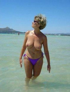 Зрелая мадам загорает на пляже в одних трусиках