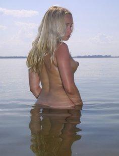 Голая девчонка на берегу моря позирует одиноко