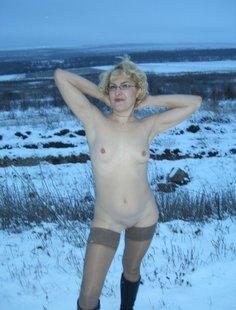 Старая баба в сапожках и чулках на снегу