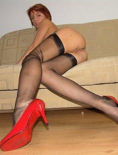 Рыжая телка в черных чулках нежится на диване