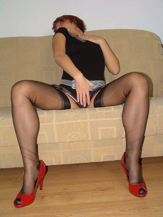 Рыжая телка в черных чулках нежится на диване 3 фото