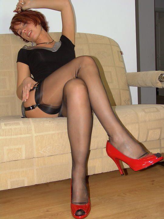 Рыжая телка в черных чулках нежится на диване 2 фото