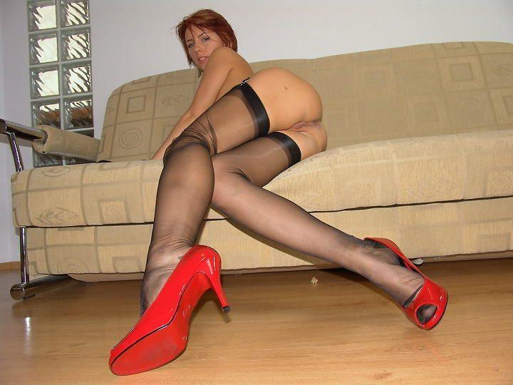 Рыжая телка в черных чулках нежится на диване 9 фото
