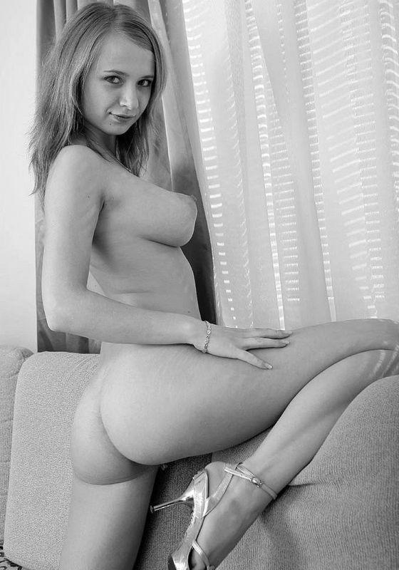 18 летняя малышка выложила в сеть свою обнаженку на диване у окна в черно-белом стиле 7 фото