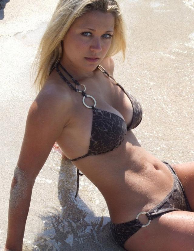 Блондиночка позирует топлес на берегу моря 2 фото