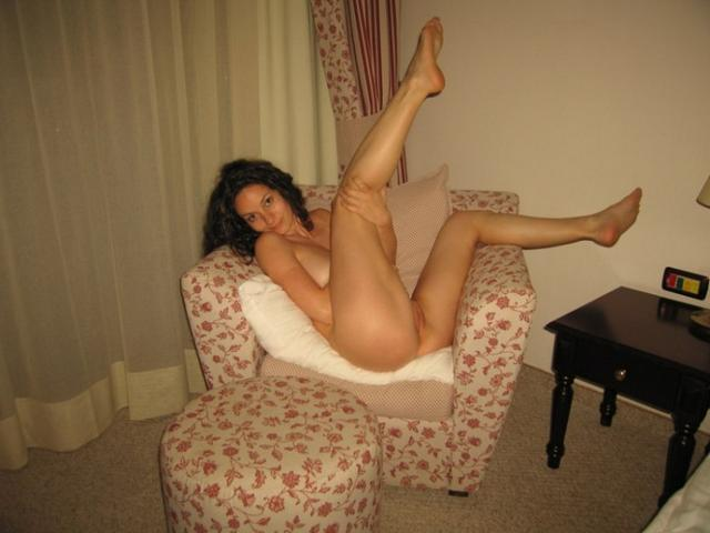 Кучерявая телка показывает в спальне большие сиськи 8 фото