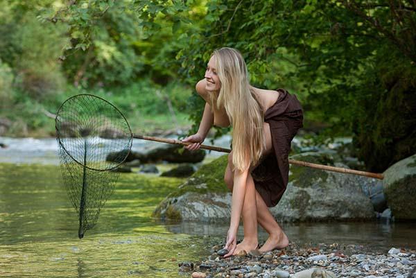 Амазонка с красивой фигурой ловит рыбу в речке 3 фото
