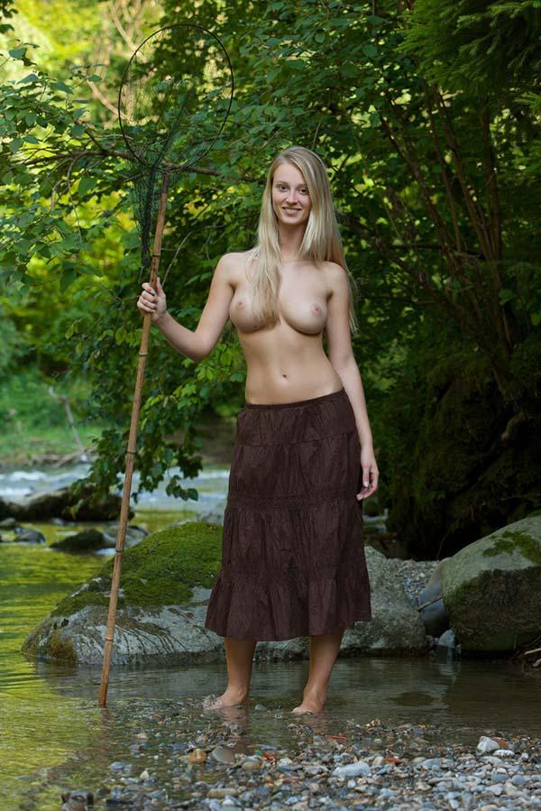 Амазонка с красивой фигурой ловит рыбу в речке 1 фото