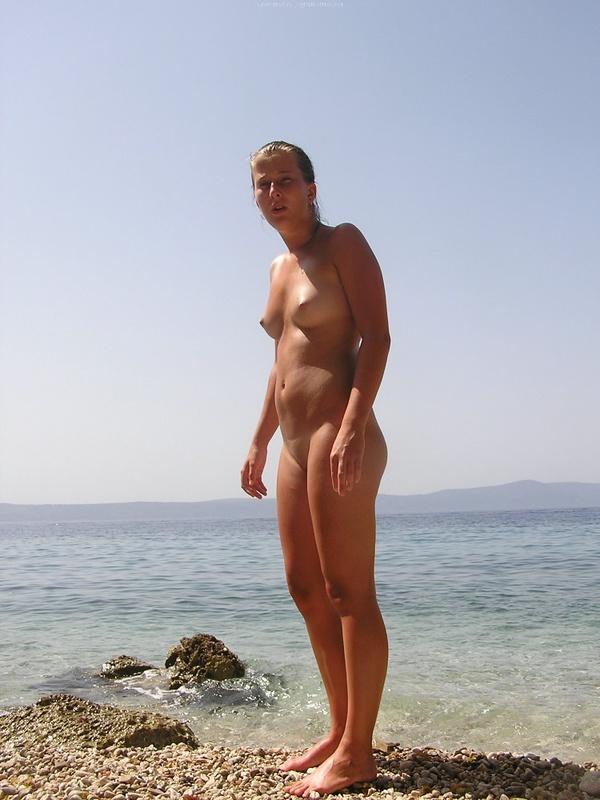 Голая туристка загорает с мужем у моря 8 фото