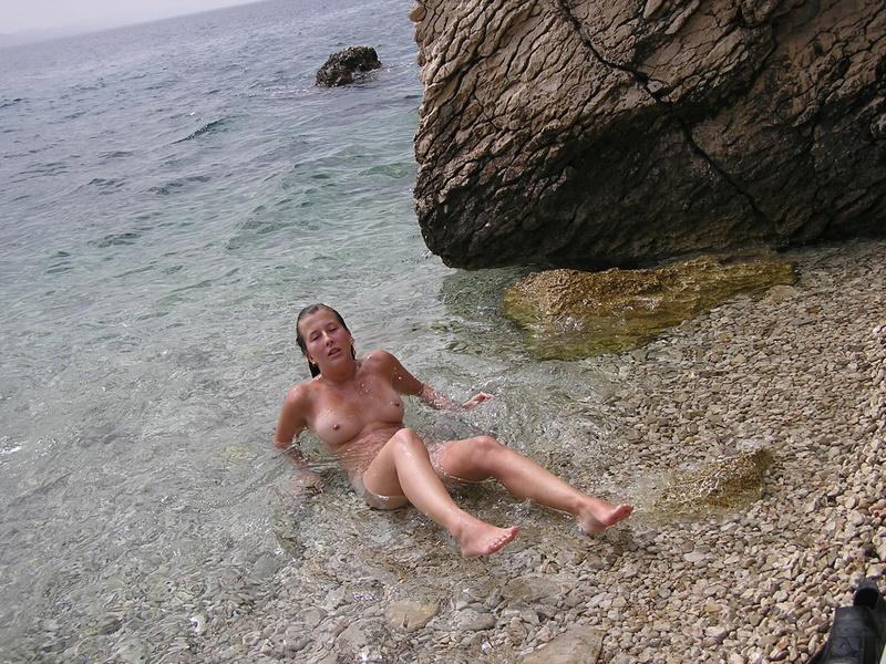 Голая туристка загорает с мужем у моря 6 фото