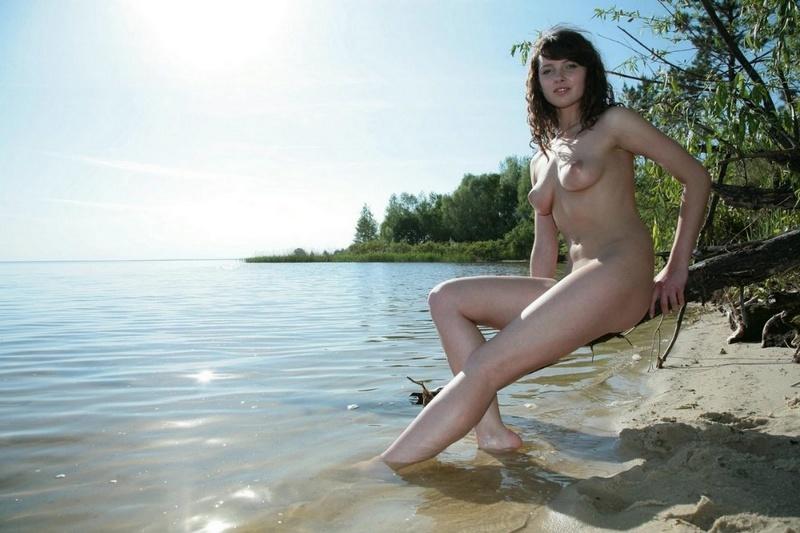 Милая и голая брюнетка на берегу реки 19 фото