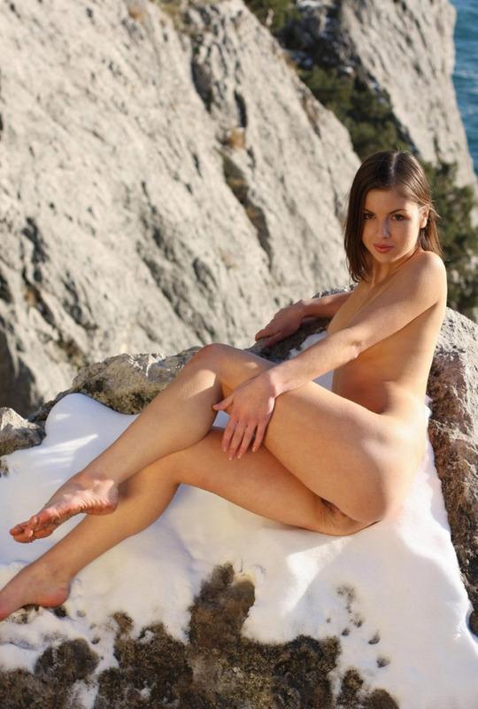 Стройная девушка с красивой грудью позирует возле моря 18 фото