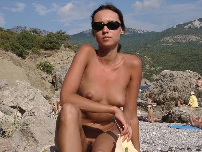 Худая туристка с интимной стрижкой загорает на нудистском пляже 14 фото