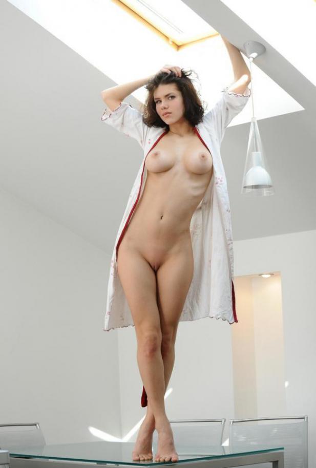 Брюнетка в легком халатике оголила грудь и киску на стеклянном столе 10 фото