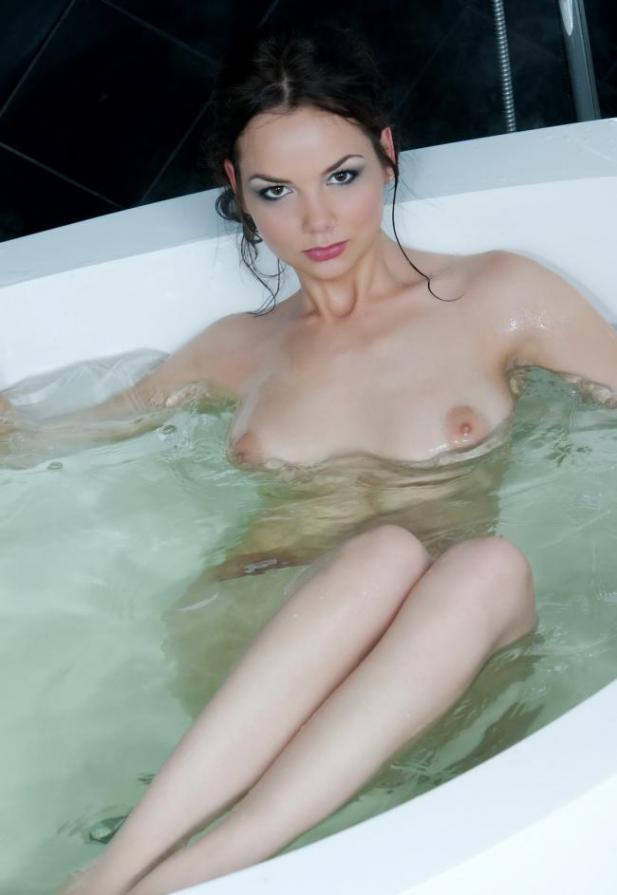 Брюнетка в легком халатике оголила грудь и киску на стеклянном столе 1 фото