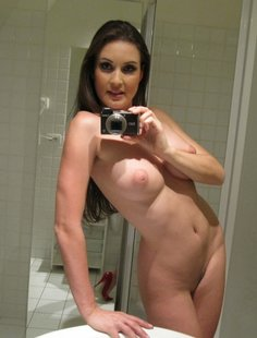 Сиськастая брюнетка позирует возле зеркала голая