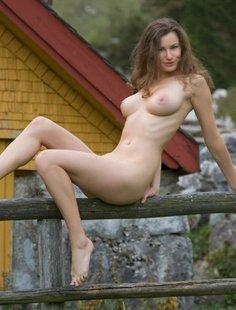 Сисятая красотка с длинными волосами позирует у своего домика в горах