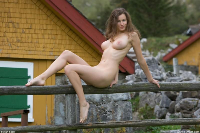 Сисятая красотка с длинными волосами позирует у своего домика в горах 1 фото