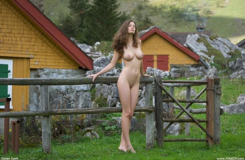Сисятая красотка с длинными волосами позирует у своего домика в горах 5 фото