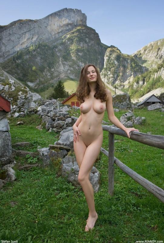 Сисятая красотка с длинными волосами позирует у своего домика в горах 26 фото