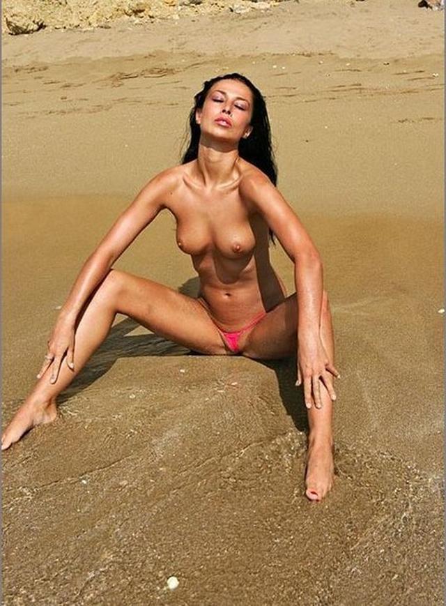 Стройная эро модель в розовых стрингах загорает на пляже