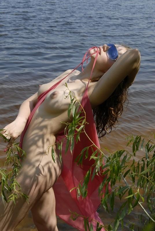 Красотка возле речки раздевается и оголяет сиськи перед мужем 13 фото