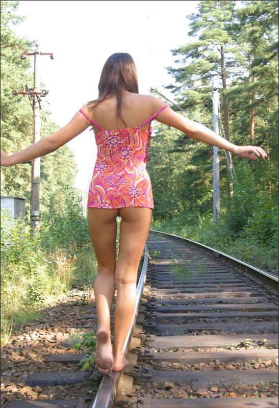 Красавица с пирсингом на животе гуляет по шпалам и раздевается 2 фото