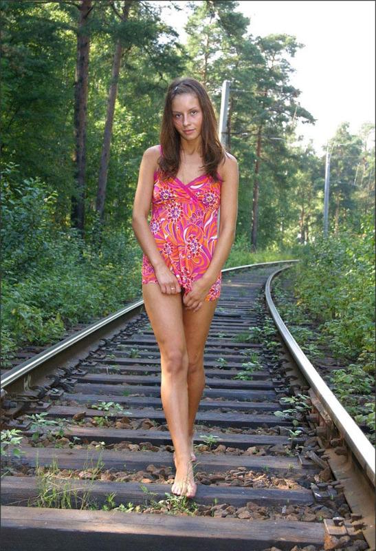 Красавица с пирсингом на животе гуляет по шпалам и раздевается 1 фото